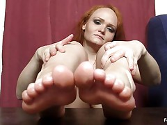 This woman really wants to wrap her feet around a cock and make it cum, but unfortunately this babe does not have a cock handily available. Therefore, this babe is making use of the next superlatively good thing, which is a nasty big dark sextoy standing up right on the table. She is caressing that with her feet.